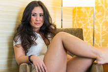 Woman Sitting In Chair With Legs Crossed Seductively