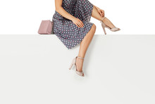 Beautiful Legs Woman Wearing Polka Dot Dress With Pink Purse Hand Bag, High Heels Shoes Sitting On White Bench. Space For Text