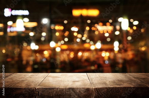 Spoed Foto op Canvas Restaurant background Image of wooden table in front of abstract blurred restaurant lights