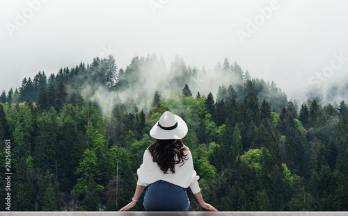 Woman in white hat looking at misty landscape with pine forests in the morning
