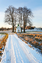A Country Road Covered With Snow And At Its End A Roadside Chapel.