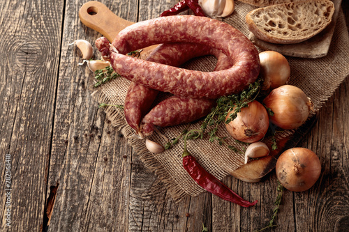 Fotografie, Obraz  Dry-cured sausage with bread and spices on a old wooden table.