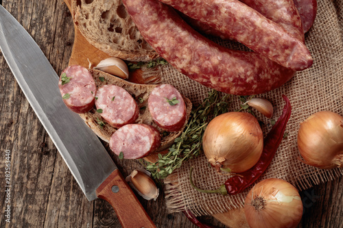 Obraz na plátně  Dry-cured sausage with bread and spices on a old wooden table.