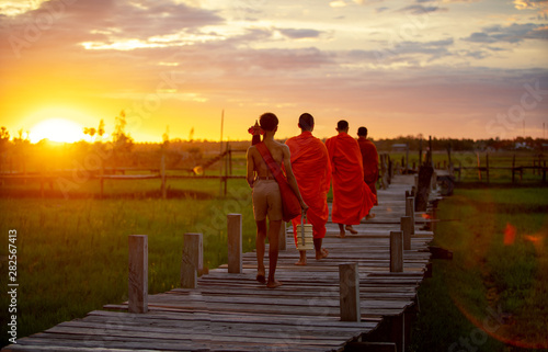Valokuva Thailand The monks and boy are walking on a wooden bridge in the sunset during