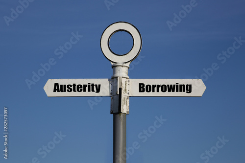 Photo Old road sign with a choice between austerity and borrowing written on it