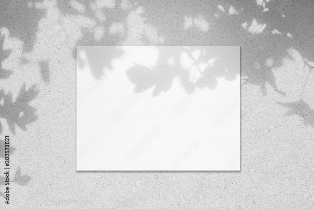 Fototapeta Empty white horizontal rectangle poster mockup with soft shadow on neutral light grey concrete wall background. Flat lay, top view