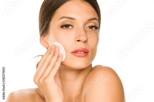 Stickers pour porte Pain Young beautiful woman claning her face with cotton pad on white background