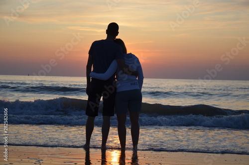 Couple amoureux devant un couché de soleil sur la plage Canvas Print