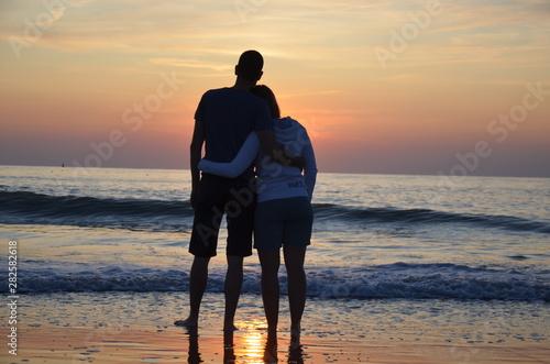 Photo Couple amoureux devant un couché de soleil sur la plage