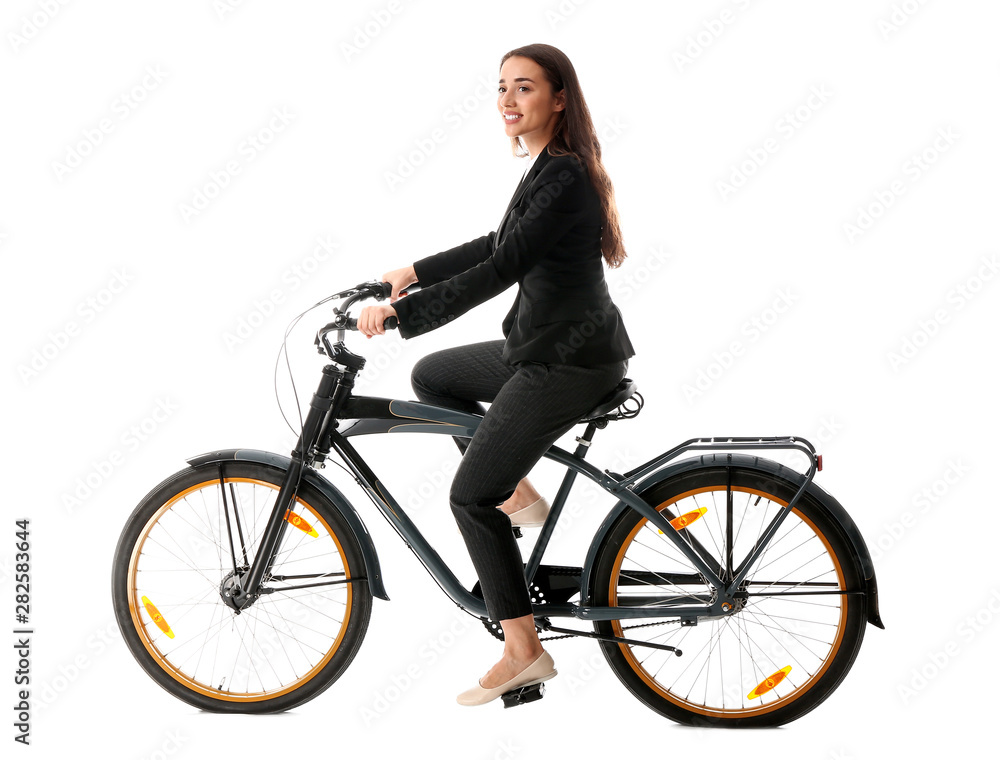 Fototapeta Young businesswoman riding bicycle against white background