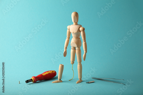 Photo Wooden figure of man with artificial prosthetic leg