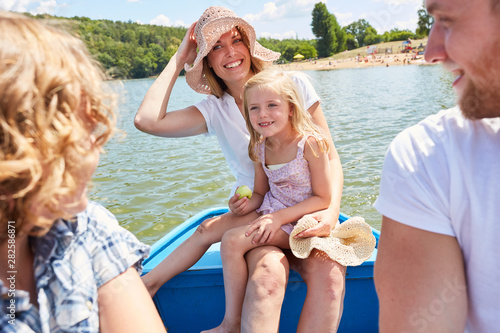 fototapeta na drzwi i meble Glückliche Familie macht Ausflug im Ruderboot
