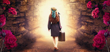 Young Redhead Lady Woman In Polka Dot Dress, Hat And Suitcase In Retro Style With Starling Bird On Shoulder Walking Out Through Stone Dungeon Cave Towards Mystical Glow. Idyllic Tranquil Fantasy Scene