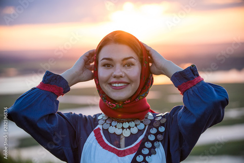Young smiling woman in traditional russian clothes on a background of the sunset Wallpaper Mural