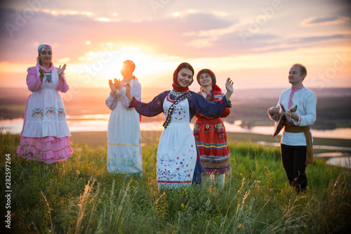 Photo sur Toile Les Textures People in traditional russian clothes standing on the field on a background on the bright sunset - a woman dancing
