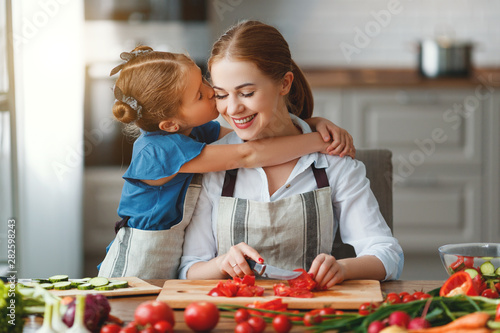 happy family mother with child girl preparing vegetable salad .