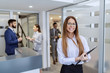 Leinwandbild Motiv Young smiling Caucasian businesswoman in formal wear holding clipboard and standing on hallway. In background her colleagues chatting.