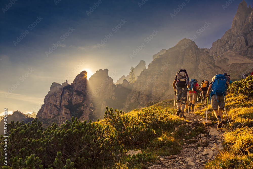 Fototapety, obrazy: Some hikers go up a mountain path in the early hours of the day