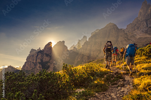 Obraz Some hikers go up a mountain path in the early hours of the day - fototapety do salonu