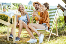 Young Friends Talking And Having Fun, While Sitting Together With Summer Drinks On The Sunbeds At The Backyard During The Sunny Day