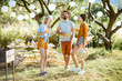 canvas print picture - Young friends having fun, standing together with drinks in the beautifully decorated backyard or garden during a festive lunch or party