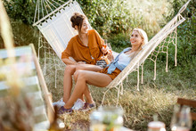 Two Young Girlfriends Relaxing With Drinks On Hammock During A Picnic In The Beautifully Decorated Garden On A Summer Evening