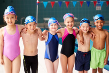 Portrait Of Children Standing On Edge Of Pool Waiting For Swimming Lesson