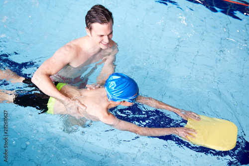 Photo sur Toile Nautique motorise Male Swimming Coach Giving Boy Holding Float One To One Lesson In Pool