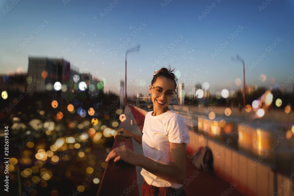 Fototapeta Bright summer lifestyle portrait of young pretty woman in eyewear, red skirt and white T-shirt, standing on the bright red bridge at evening with city background and blurred bokeh.
