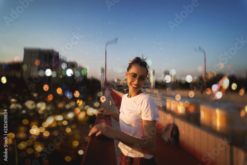 Fototapeta Bright summer lifestyle portrait of young pretty woman in eyewear, red skirt and white T-shirt, standing on the bright red bridge at evening with city background and blurred bokeh. obraz