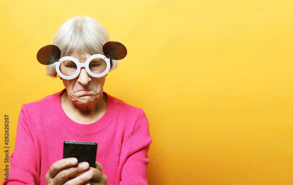 Fototapety, obrazy: old grandmother is talking to her grandchildren by phone, smiling and greeting them.