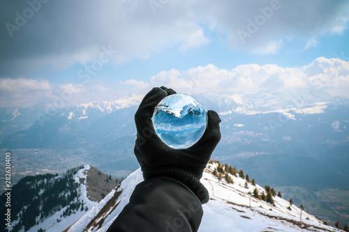 Main tenant une boule de verre face à une montagne