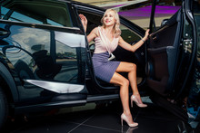 Chauffeur Gentleman Helping To Young Business Woman In Sexy Dress And High Heel Footwear After Night Party In Club , To Get Out From A Luxury Car