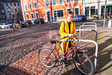 Young Woman In Yellow Coat Sta...
