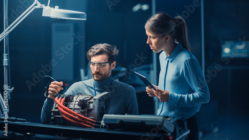 Male and Female Automotive Engineers with a Tablet Computer and Inspection Tools are Having a Conversation While Testing an Electric Engine in a High Tech Laboratory with a Concept Car Chassis Wallpaper Mural