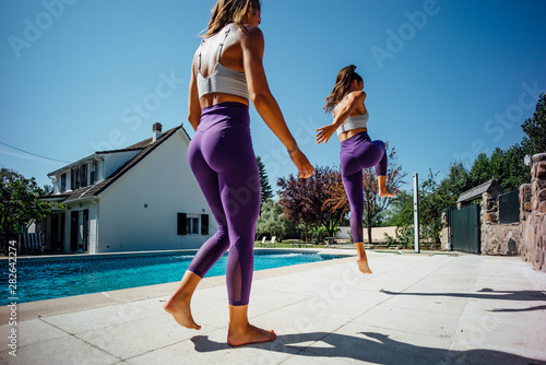 Two female twin sisters doing gymnastic exercise beside pool Canvas Print