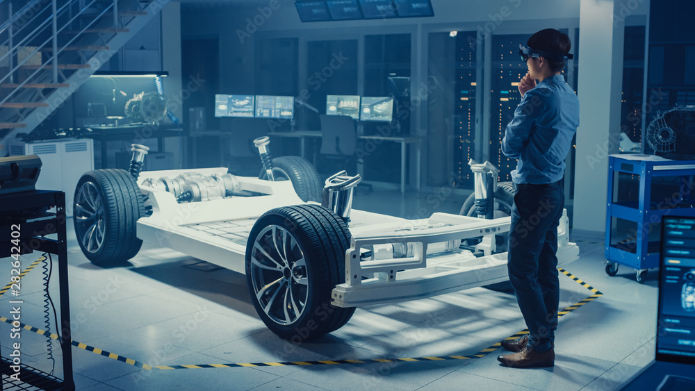 Fototapeta Automotive Engineer Working on Electric Car Chassis Platform, Using Augmented Reality Headset. In Innovation Laboratory Facility Concept Vehicle Frame Includes Wheels, Suspension, Engine and Battery.