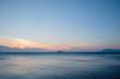 Ship sailing at horizon in sea at sunset.