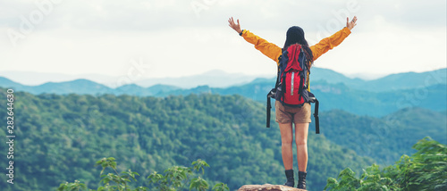 Fotografia, Obraz Women hiker or traveler with backpack adventure feeling victorious facing on the mountain, outdoor for education nature on vacation
