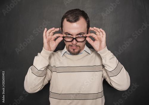 Fotografía  Handsome strict teacher in eyeglasses looking at you on blackboard