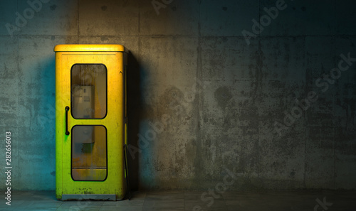 Obraz na plátně  Single old yellow phone booth in retro style standing on the floor in front of the concrete wall at night time