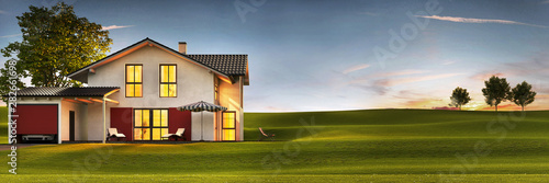 Fototapeta Evening view of a modern house with a lawn and a terrace. obraz