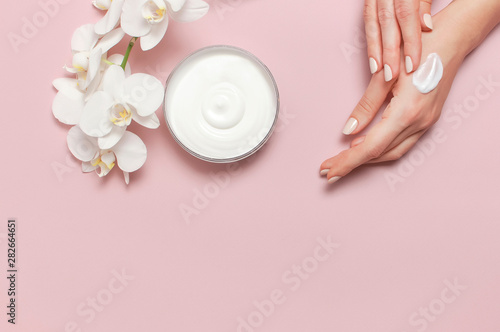 Cadres-photo bureau Spa Young woman moisturizes her hand with cosmetic cream lotion opened container with cream body milk White Phalaenopsis orchid flowers on pink background Flat lay top view minimalism style Beauty concept