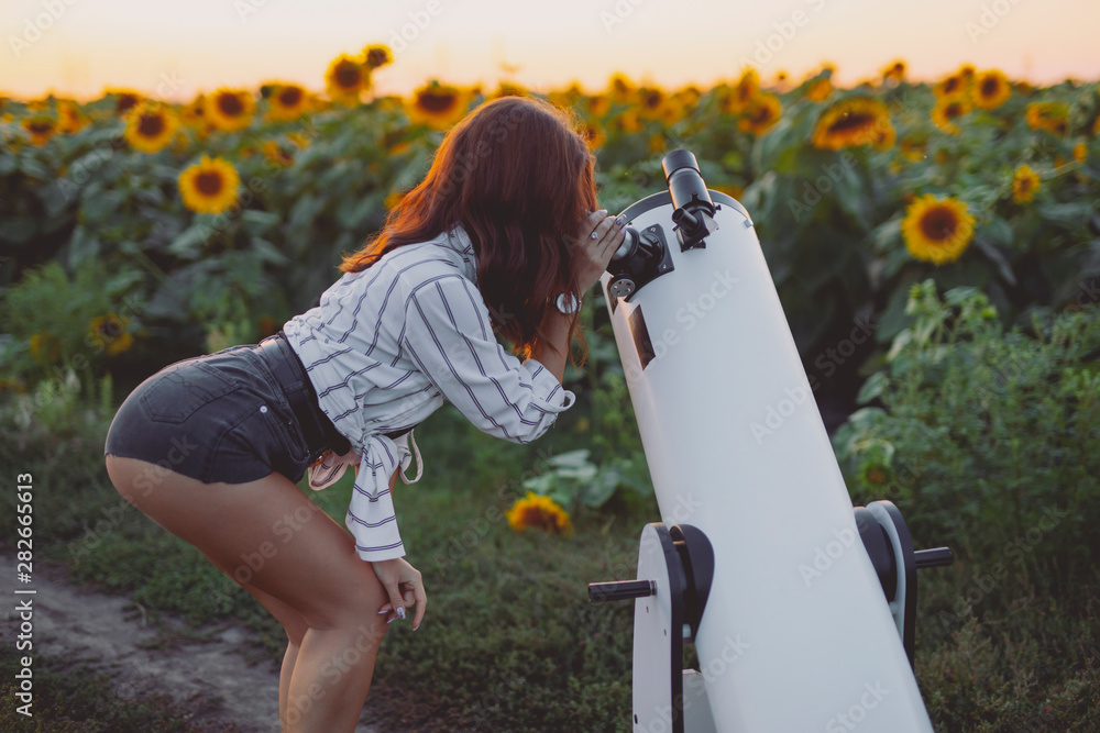 Fototapety, obrazy: Sexy woman looking through telescope