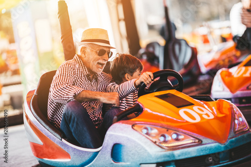 Garden Poster Amusement Park Grandfather and grandson having fun and spending good quality time together in amusement park. They enjoying and smiling while driving bumper car together.