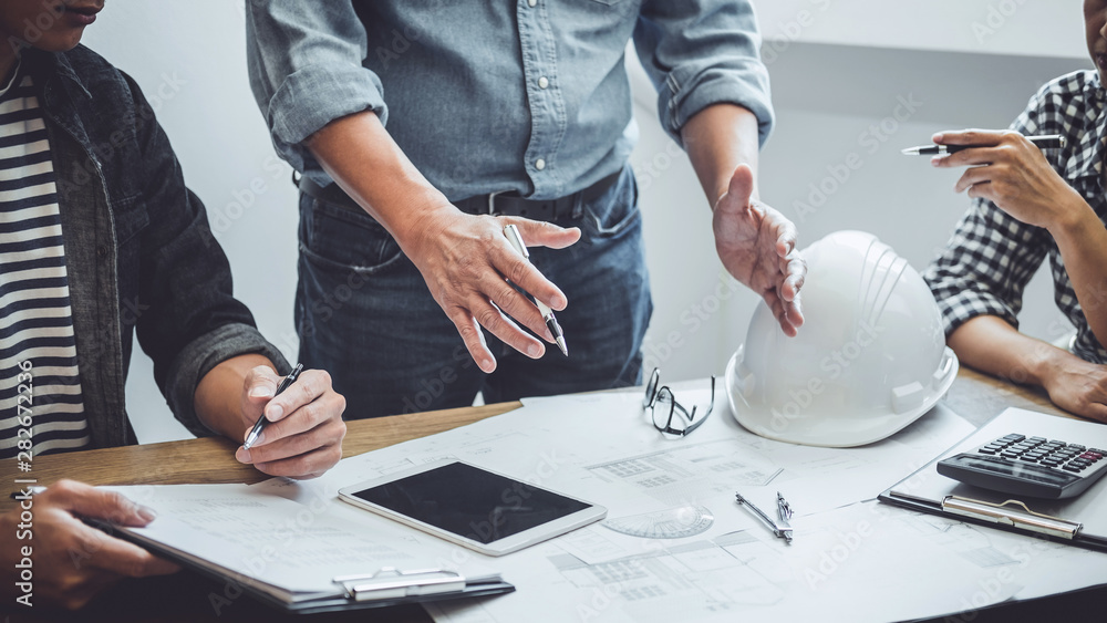 Fototapeta Construction and structure concept of Engineer or architect meeting for project working with partner and engineering tools on model building and blueprint in working site, contract for both companies