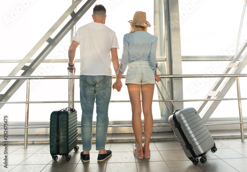 Fotografering  Young couple looking through airport window, back view