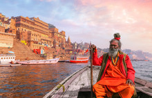 Indian Sadhu Baba Takes A Boat Ride On River Ganges Overlooking The Historic Varanasi City Architecture At Sunset