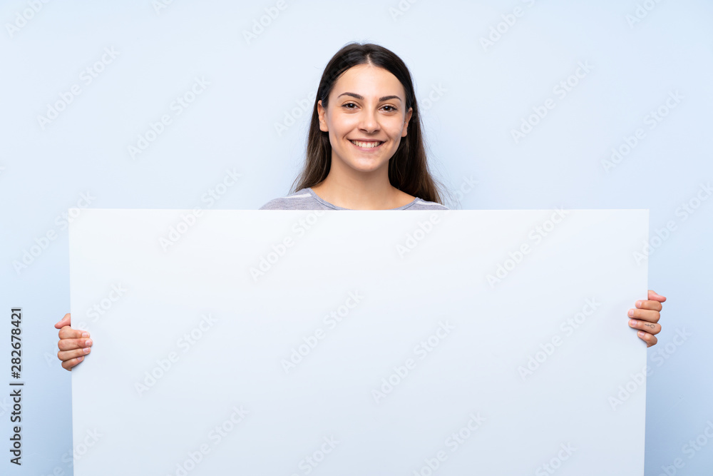 Fototapety, obrazy: Young brunette woman over isolated blue background holding an empty white placard for insert a concept