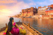 Leinwanddruck Bild - Ancient Varanasi city architecture with Ganges river bank. Indian female tourist enjoy boat ride on the river Ganges at sunset